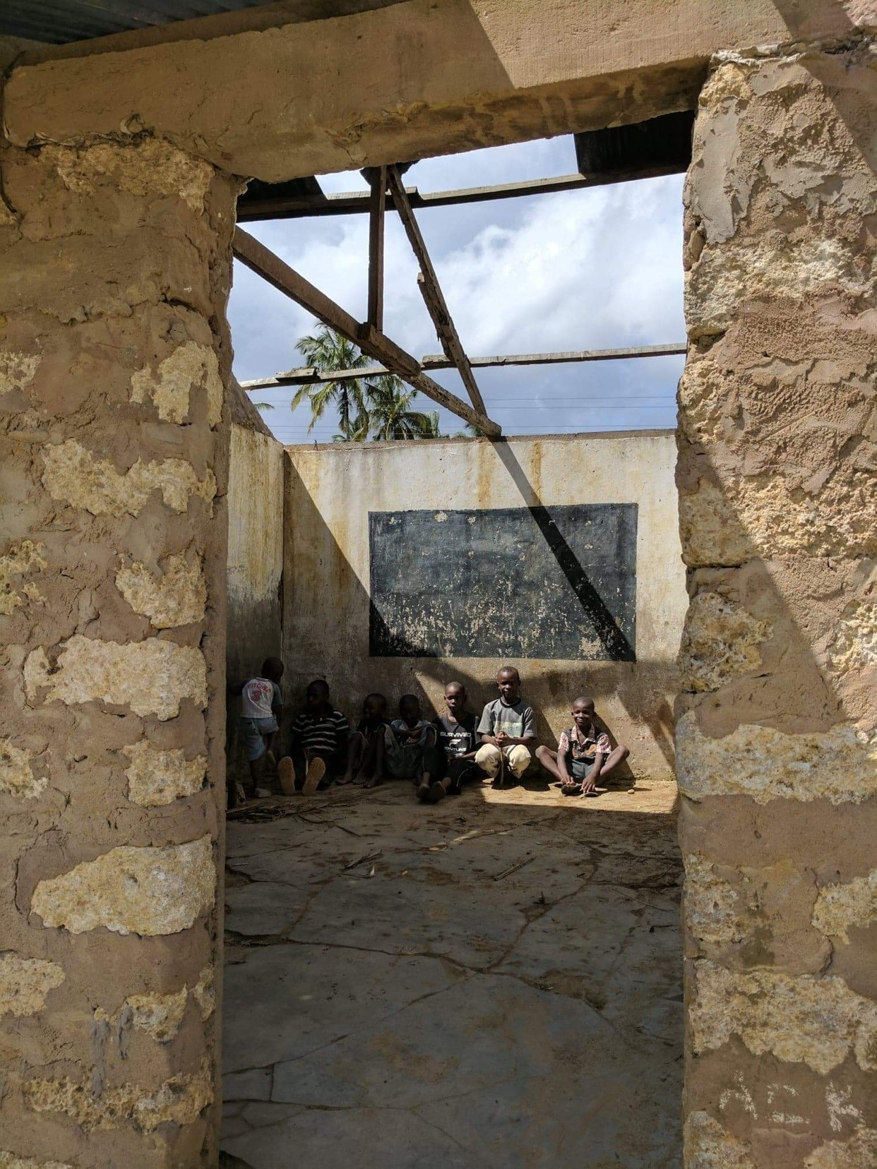 Kids from the Village of Lutsanga sitting in empty school.