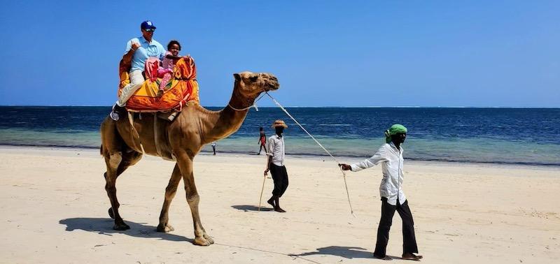 Jason Sucher and Bella Van Leeuwen riding a camel on the beach.